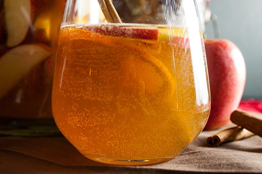 Cider Ginger Beer Sangria in a no stem wine glass garnished with cinnamon stick