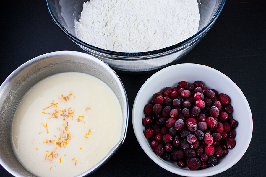 Cranberry Orange Muffin flour mixture clear bowl, wet mixture in metal bowl, frozen cranberries in small white bowl