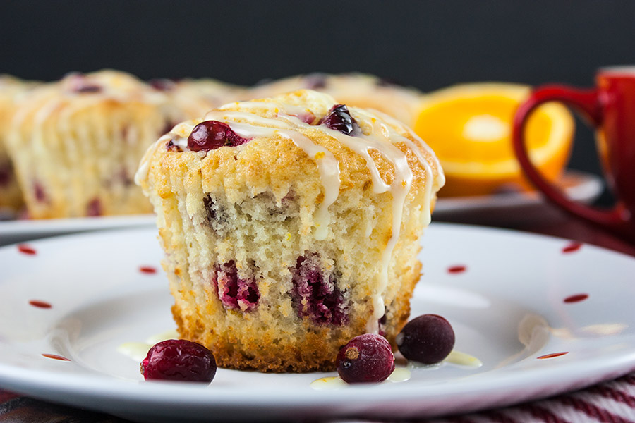 cranberry orange muffin on white plate with red dots
