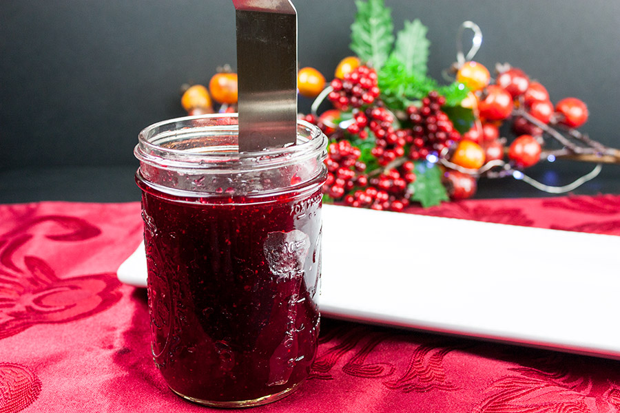 cranberry sauce in a glass jar with a thin metal spatula running along the inside of the jar