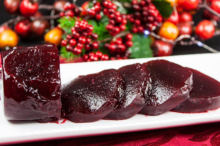Cranberry Sauce in the shape of a jar or can on a white serving dish with cranberries in the background