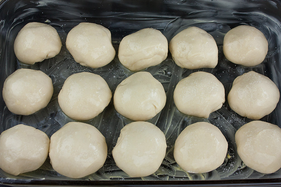 dough balls placed in a butter baking dish