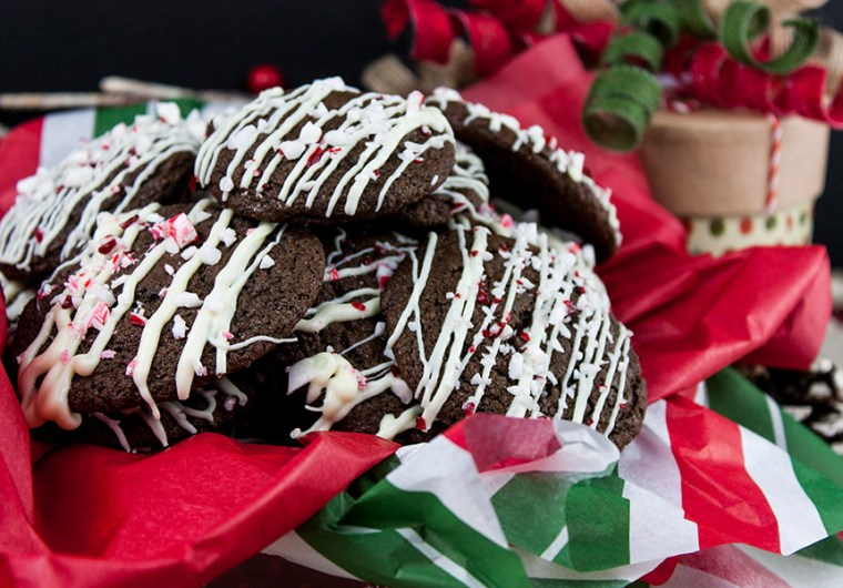 Chocolate Peppermint Cookies stacked in tin with red, white and green tissue paper