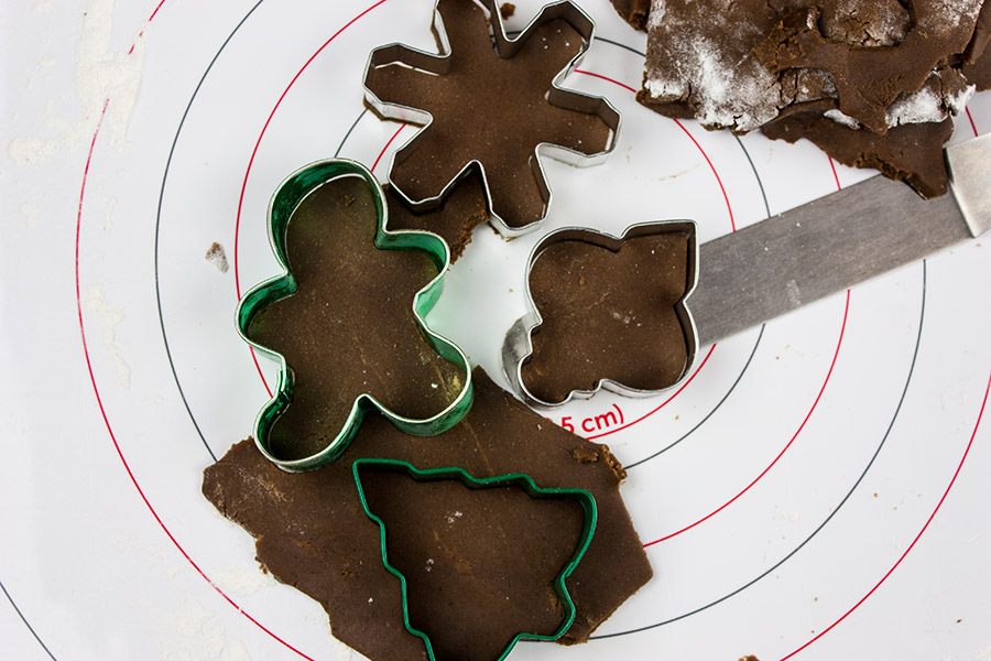 dough cut into star gingerbread man Christmas tree and ornament on pastry mat
