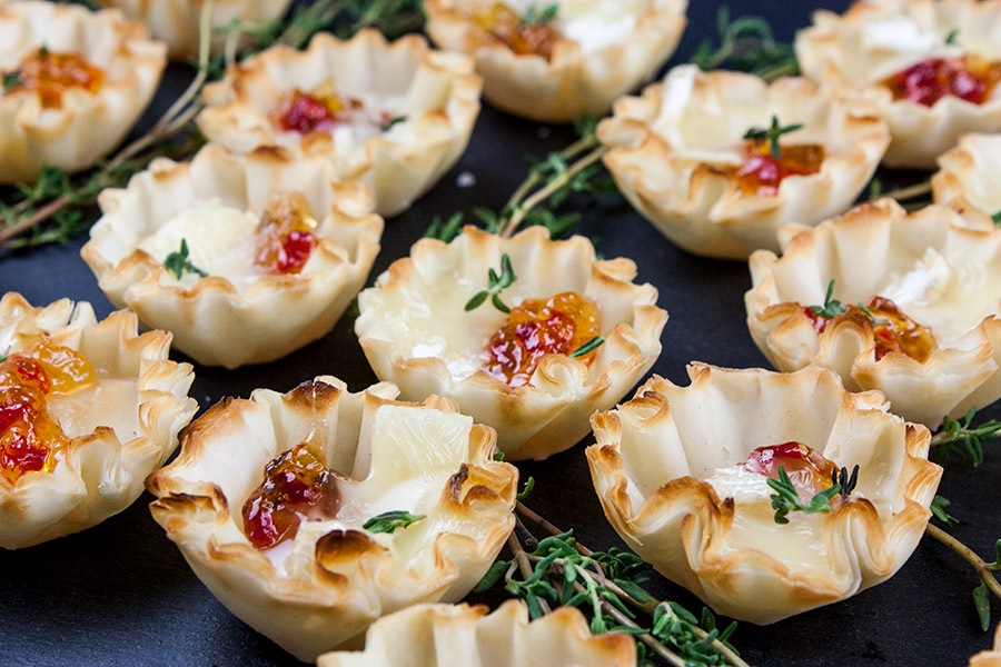 Pepper Jelly Brie Bites - Crispy phyllo shells filled with slightly spicy pepper jelly topped with creamy brie cheese. Sweet and spicy bites of flaky deliciousness!