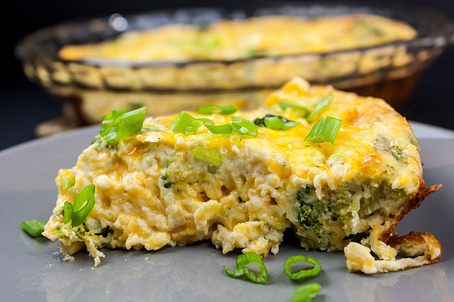slice of crustless cheddar broccoli quiche on gray plate garnished with diced green onions