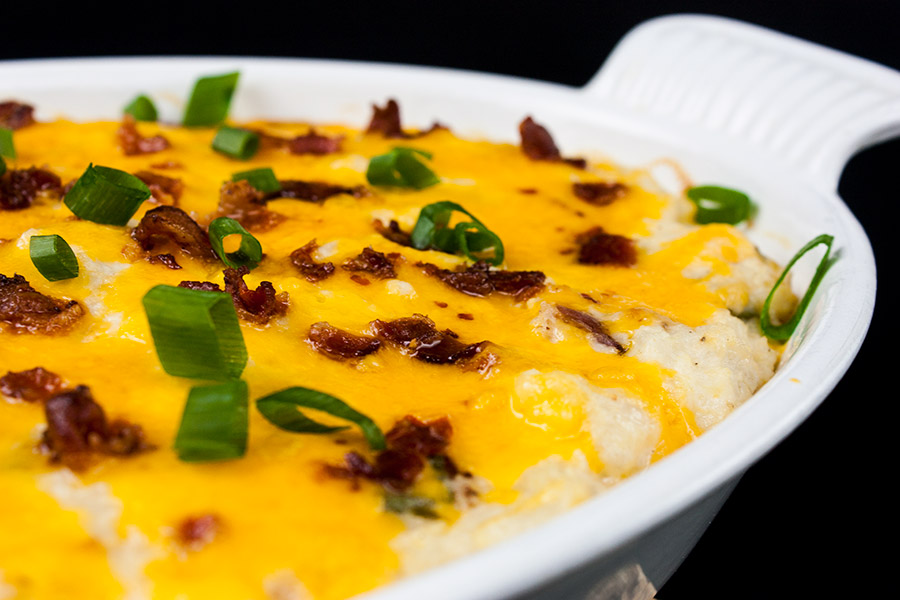 loaded cauliflower mash casserole baked in a white casserole dish garnished with green onions