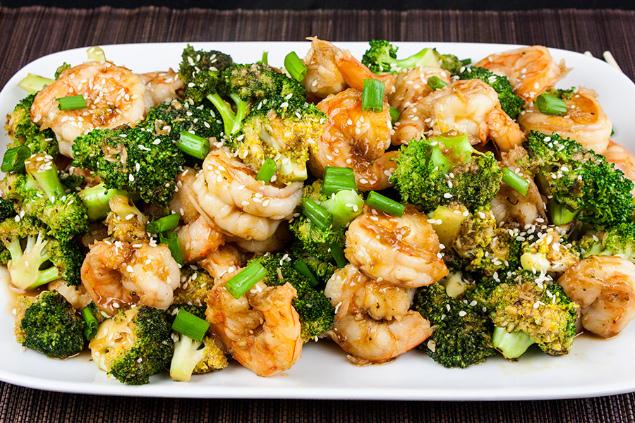 shrimp and broccoli stir fry on white platter garnished with green onions and sesame seeds