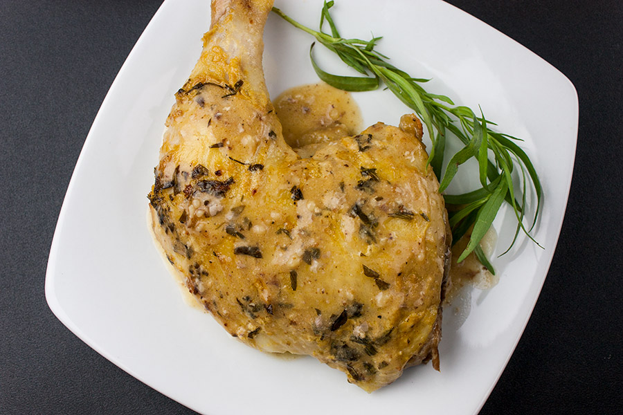 Roasted Chicken with Dijon Cream Sauce on a white plate garnished with fresh tarragon