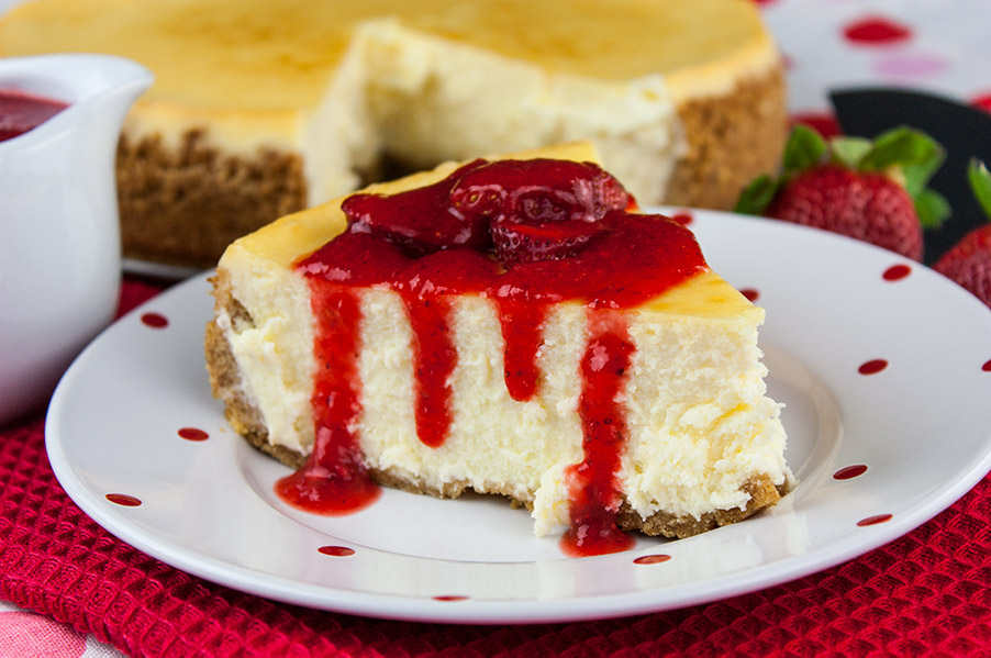 Smooth and Creamy Cheesecake on white plate with red dots drizzled with fresh strawberry coulis