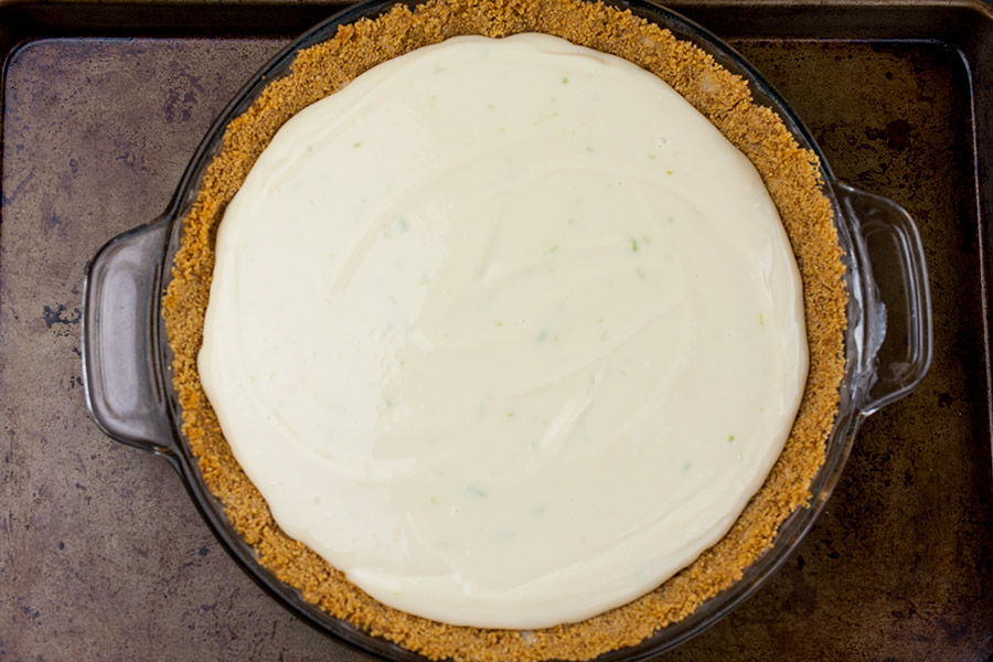 unbaked Key Lime Pie batter poured into baked graham crust