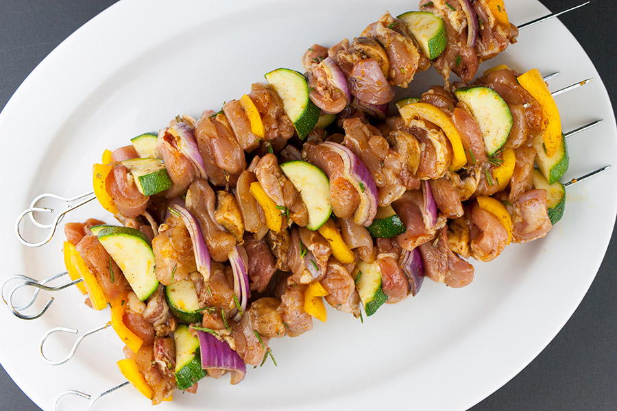 Orange Rosemary Chicken Kebabs skewered on a white platter