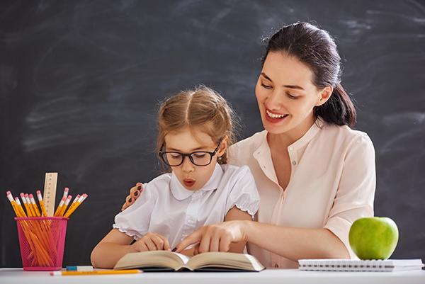 A child sounds out words in a book with the help of a teacher.