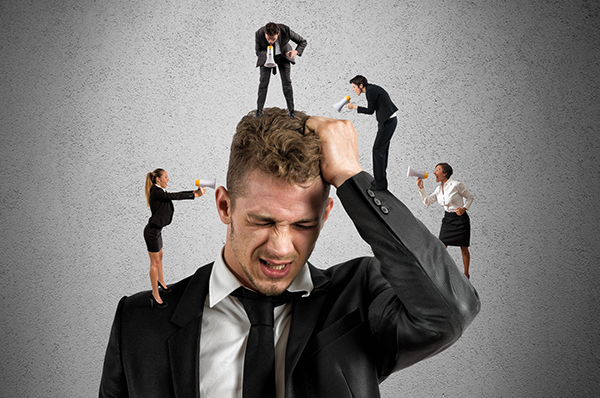 A man in a suit grabs his hair as many small people are perched on his arms, shoulders, and head, shouting at him through megaphones. This symbolizes the feeling of an overloaded brain that all of us, but especially dyslexics often feel. This blog offers some suggestions for brain management to help with that feeling. Help for adults with dyslexia is available.