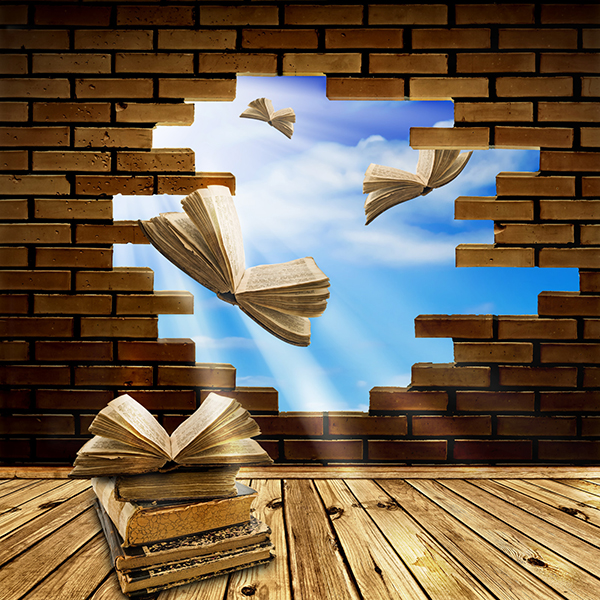 A pile of books take wing like butterflies and fly outdoors into a blue sky through a broken hole in a brick wall.