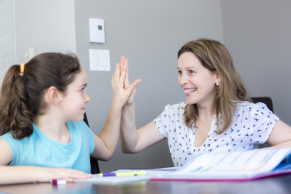 A mother and her dyslexic daughter work together on homework at at table and high five each other when finished.