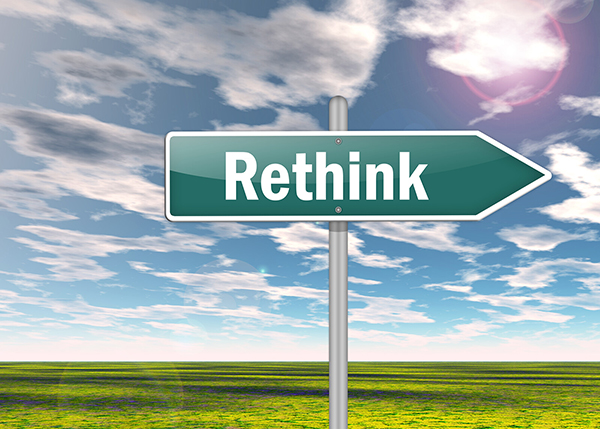 "A street sign type sign with an arrow at one end says the word ""Rethink"" against a background of blue sky, white clouds, and green grass."