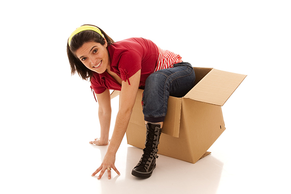 A woman crawls out of a small cardboard box, illustrating the principle of thinking outside the box when helping children with language based learning difficulties like dyslexia change their point of view from one based on fear to one based on curiosity and a sense of possibility.