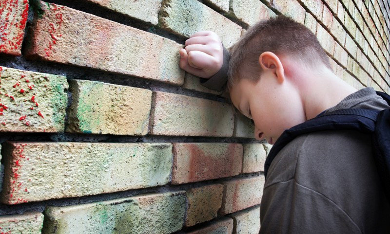 A frustrated boy leans his head against a brick wall. He may be recieving reading intervention to help with his dyslexia, but sometimes learning to read is not enough for dyslexics. What more do they need?
