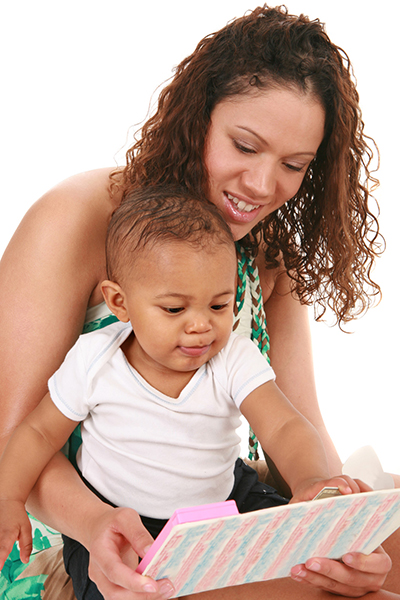 A mother reads to her baby and lets him interact with the page because she is raising readers from birth.