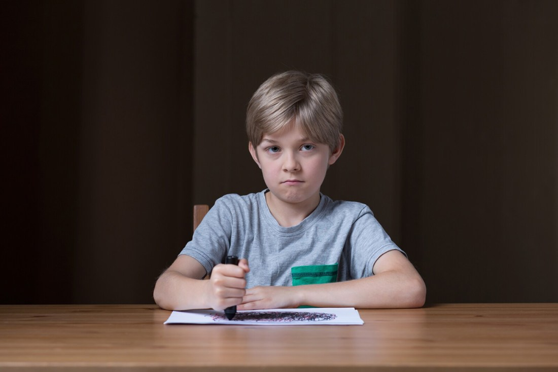 A boy sits at a table, scribbling a picture of an angry black cloud. Drawing is a way of helping dyslexic children illustrate their feelings when they are stressed, especially about the uncertainty of new circumstances and learning at home.