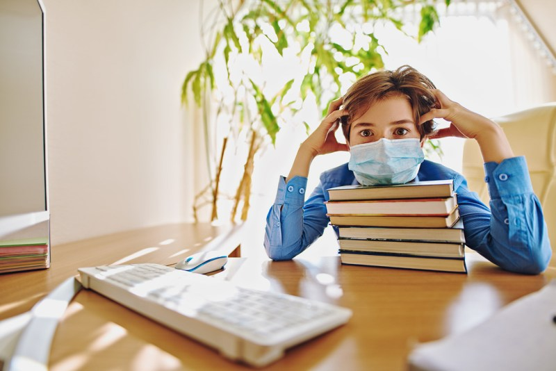A school-age boy wearing a mask sits at home at a desk with a computer and a pile of books. He looks at the viewer, holding his head in both hands, resting his chin on the pile of books. He looks overwhelmed. How can parents help dyslexic children adapt to virtual school?