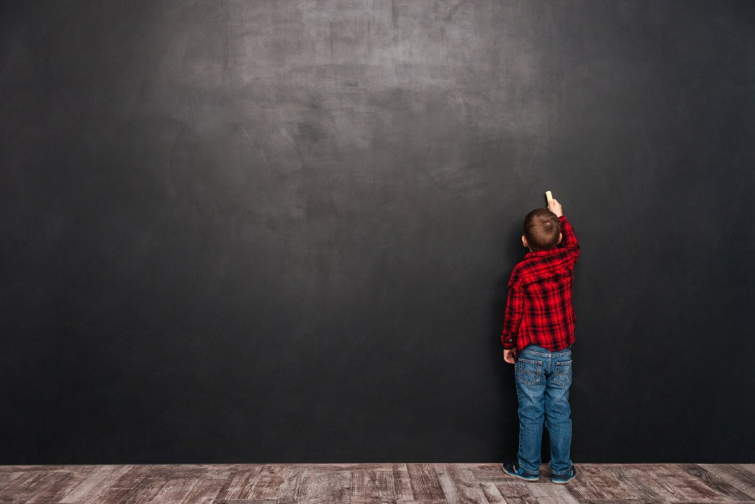 A little boy in a red and black plaid shirt and bluejeans stands in front of a blackboard wall with a piece of chalk in his hand. Writing on a vertical surface is one of several affordable ways to make learning fun for young kids.
