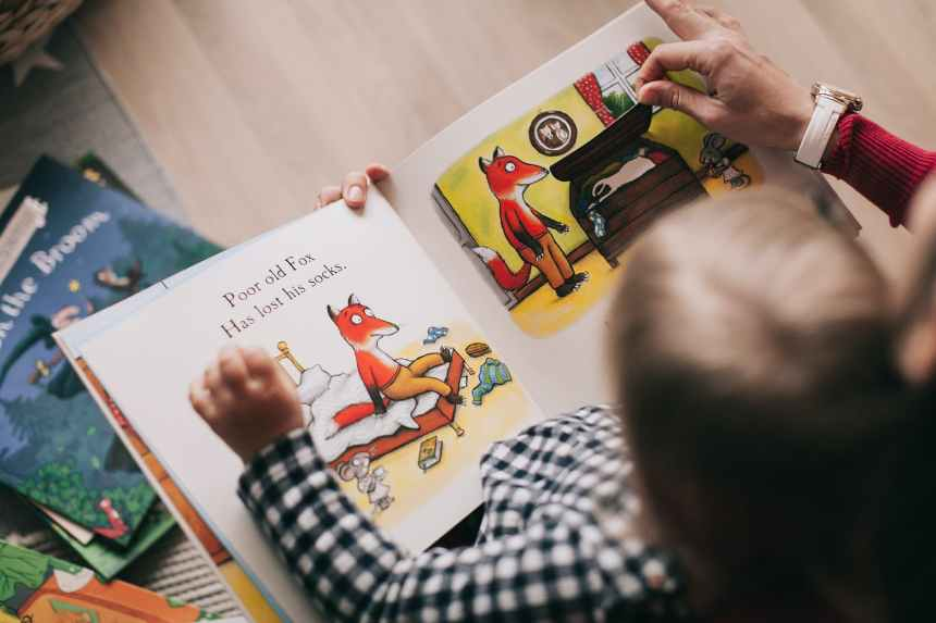 A mother reads to her baby from a picture book. The power of stories during difficult times can also lay a preliteracy foundation for very young children, which will benefit them academically when they enter school.