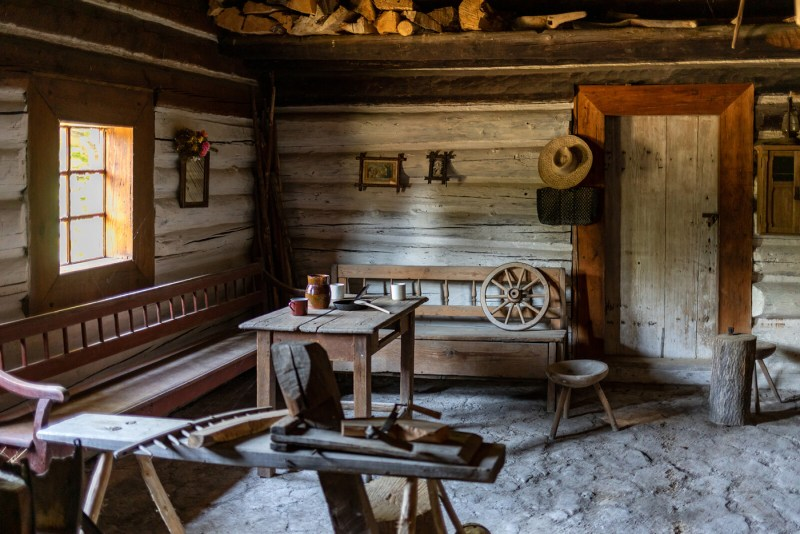 An indoor scene of a nineteenth century cabin with a dirt floor, log walls, and handmade wooden furniture and tools.
