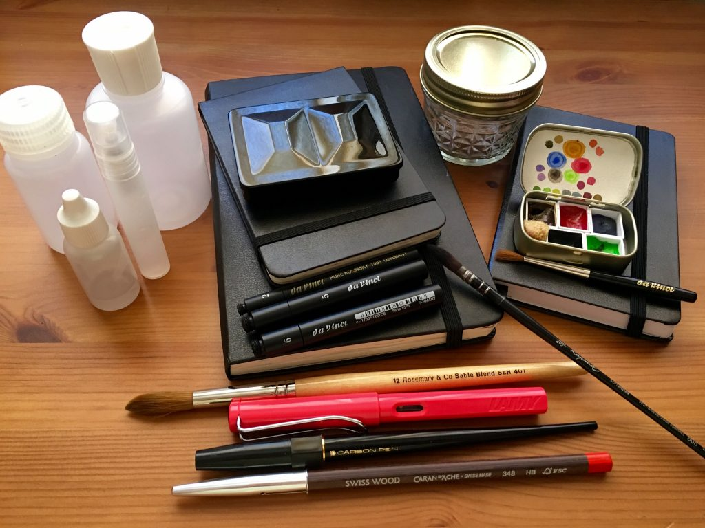 Travel watercolor palette set-up with Whiskey Painters palette, pens, Altoids tin, brushes Moleskine, Leuchtturm 1917 sketch journals, plastic Nalgene bottles, mason jelly jar, Da Vinci brushes, fountain pens Caran D'ache Swiss Wood pencil
