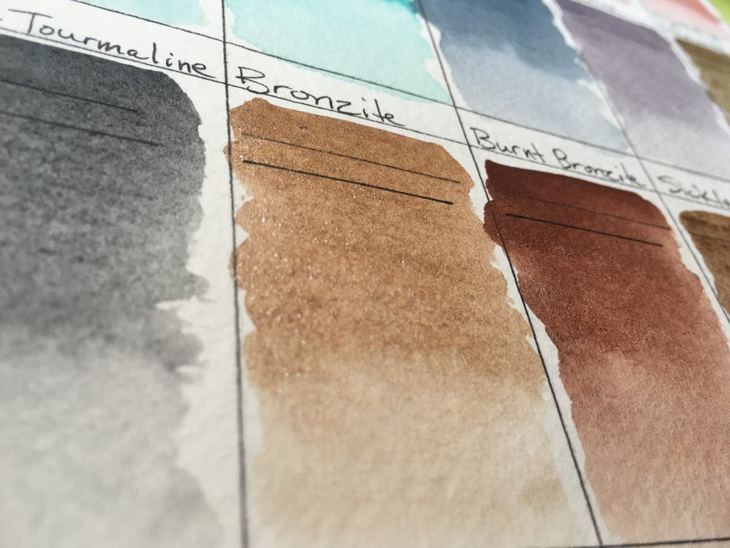 Daniel Smith PrimaTek watercolors swatches on Strathmore 400 series watercolor paper black tourmaline, Bronzite, Burnt Bronzite