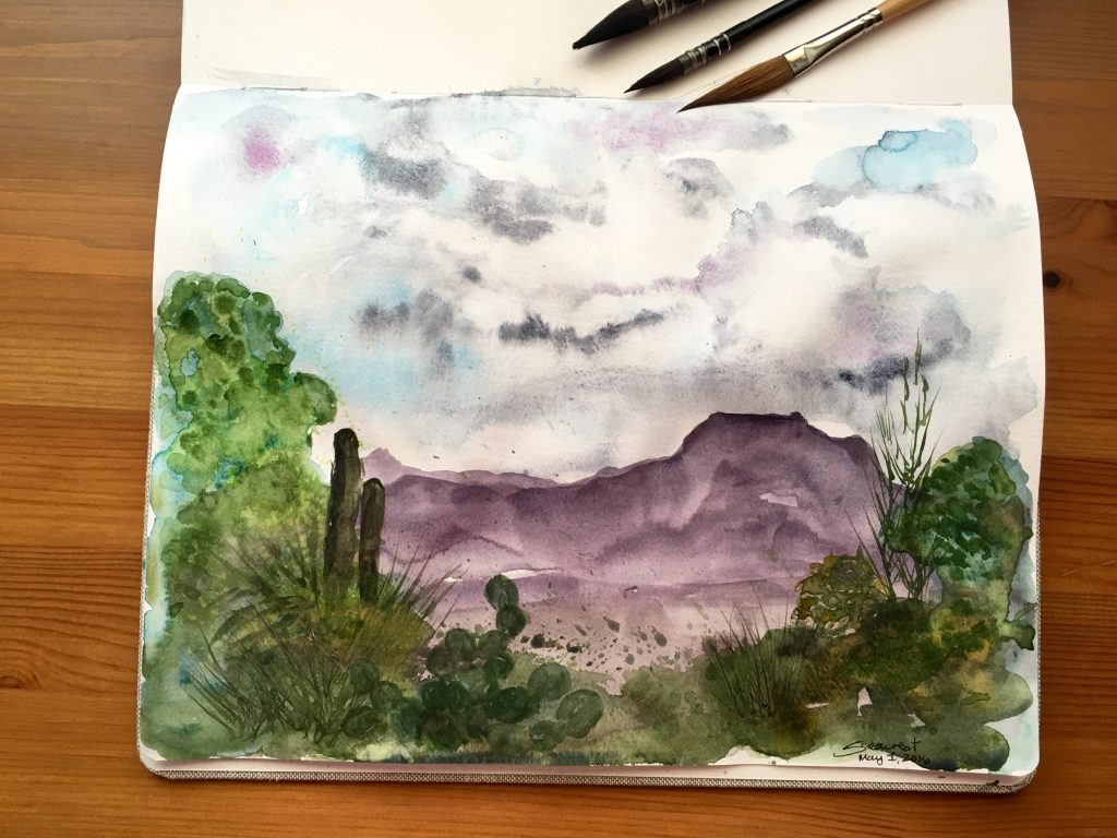 Desert Painting of the Tucson Mountains in a Handbook Travelogue Watercolor Journal in Grand Portrait size- using Moonglow, Undersea Green, Cascade Green, and Payne's Gray. The sky is DS Payne's Gray and two Holbein colors- Cobalt Violet Light and Manganese Blue Nova.