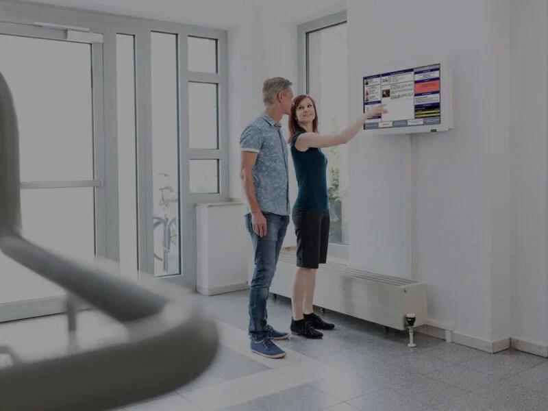 junges Paar betrachtet Infoboard im Hauseingang