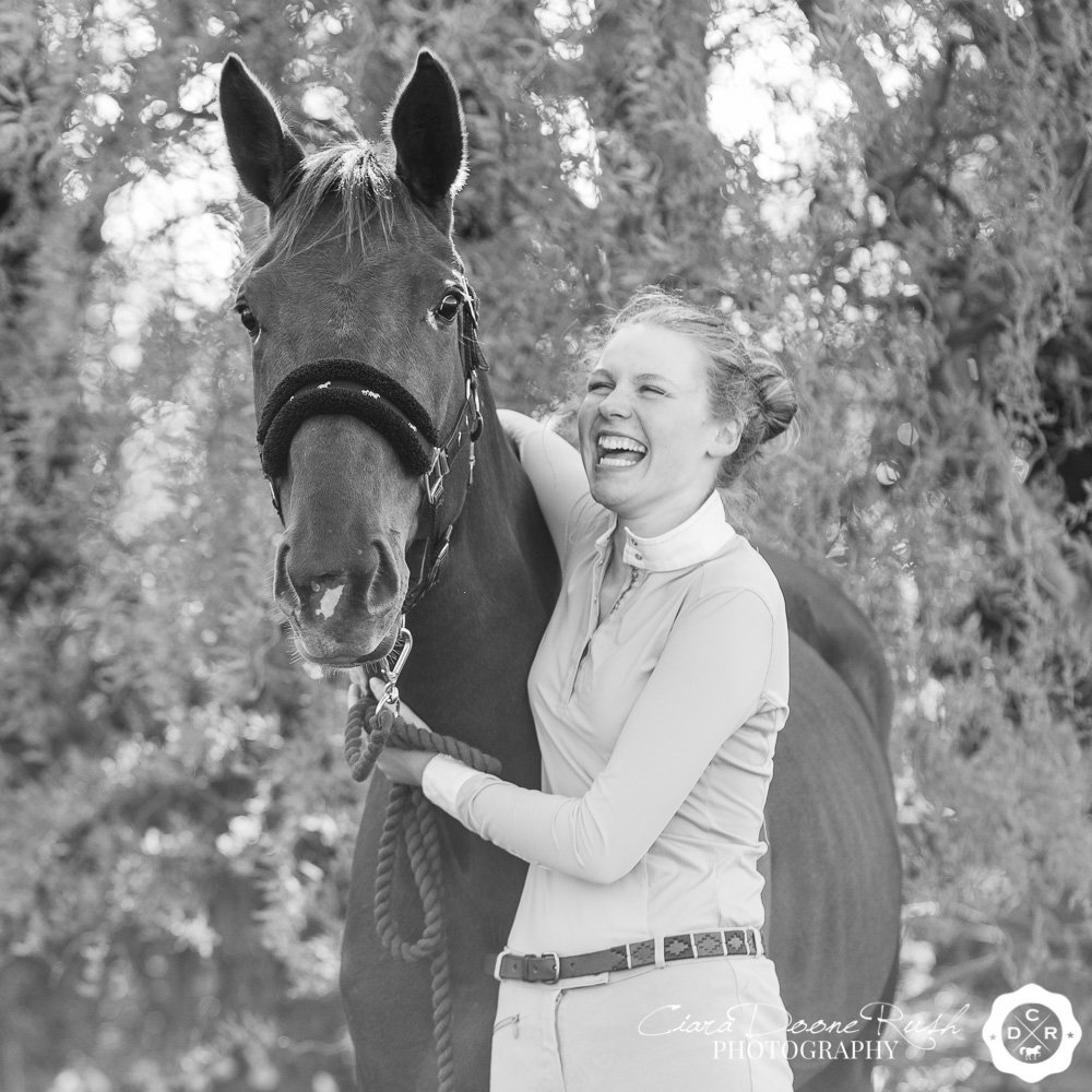 A black and white photo of a girl laughing at her horse