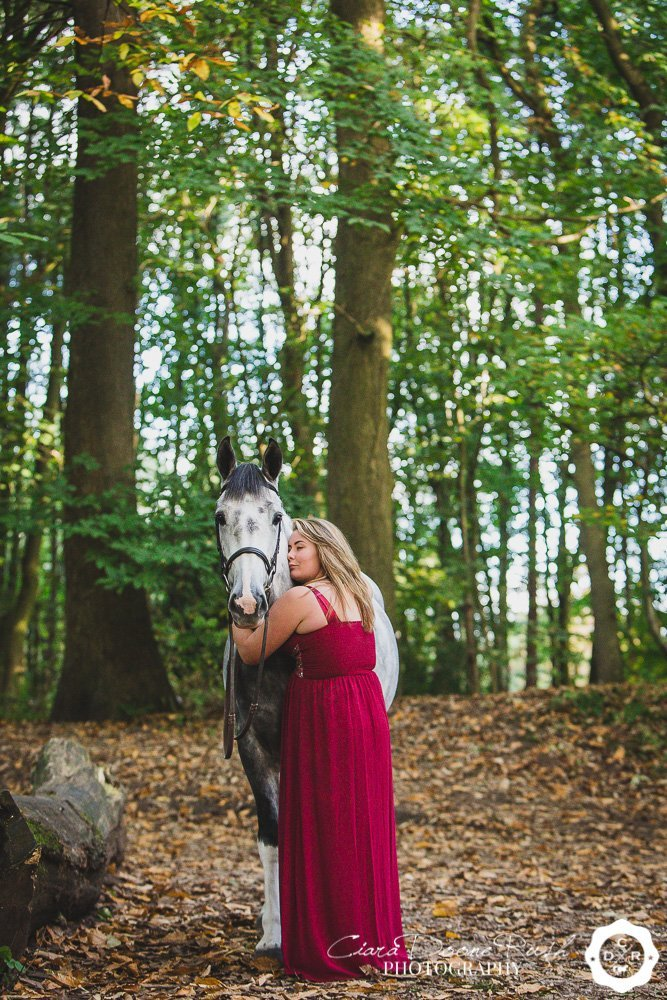 girl in a dress with horse in forest