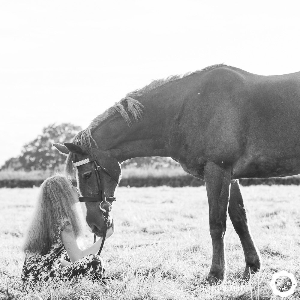 a teenager sitting with her horse
