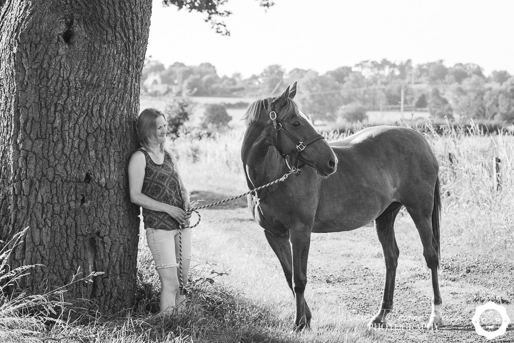 woman leaning against a tree with her horse