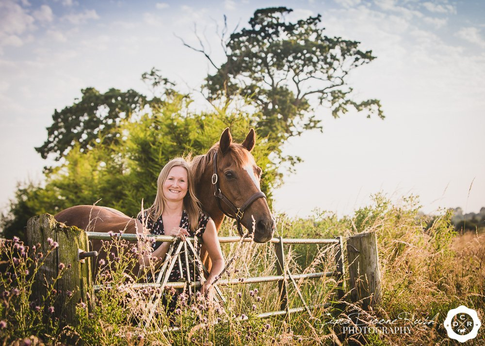 a woman leaning against a gate with her mare