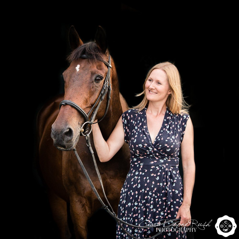 a woman and her horse on a black background