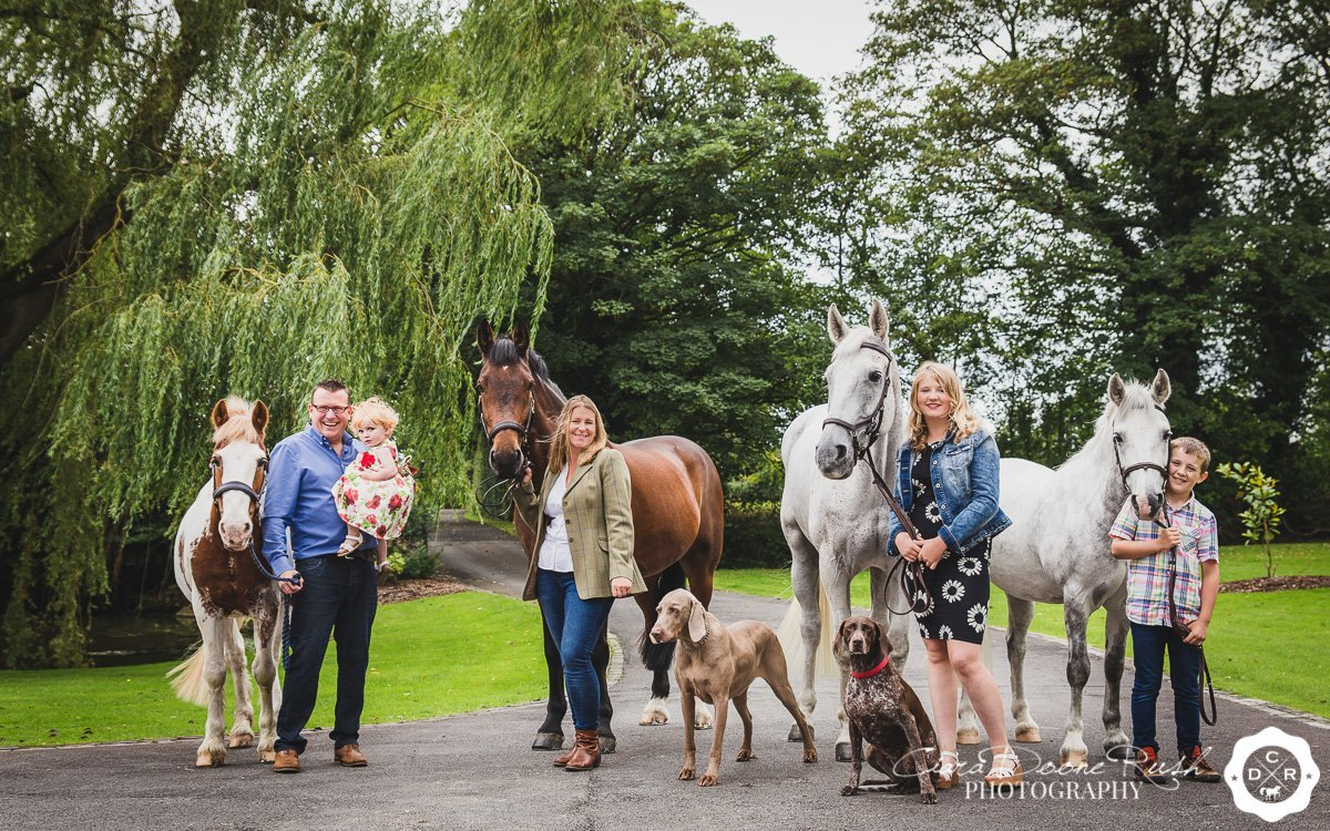 a family with their horses and dogs