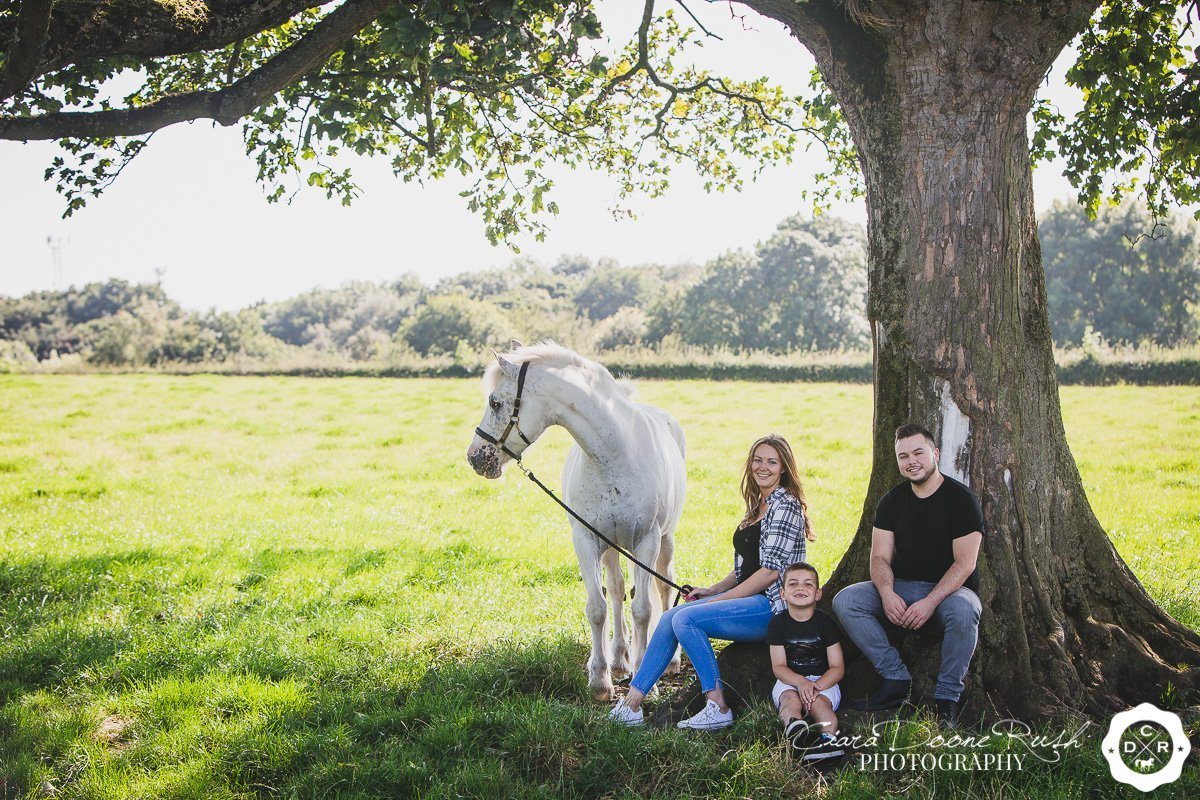 a family and their horse under a tree