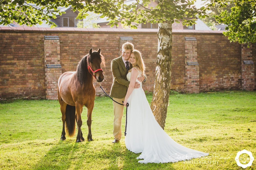 a bride and groom with their horse on a photo shoot