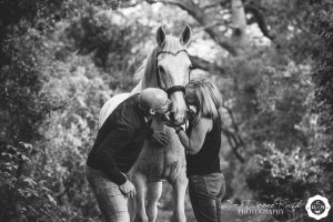a couple kissing their horse on a photo shoot