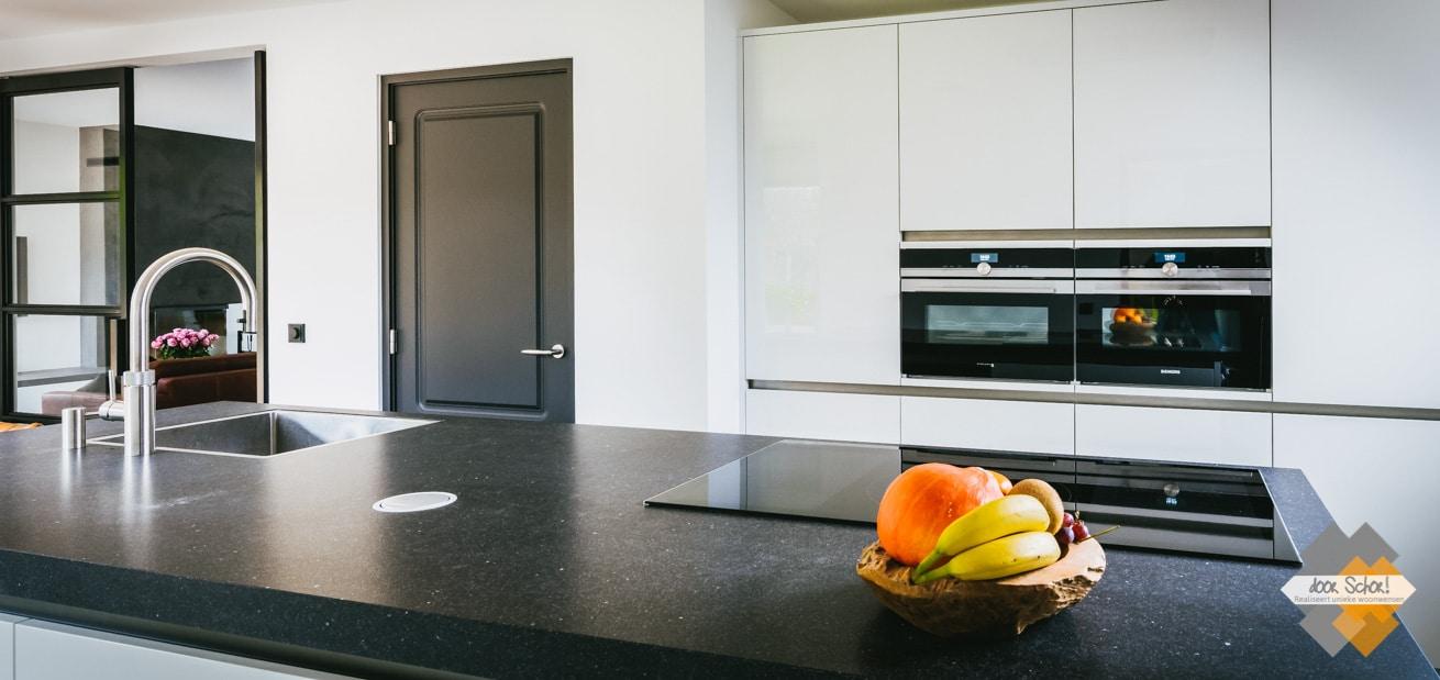 Dik granieten keukenblad met een mat witte keuken en fraaie donker grijze deuren