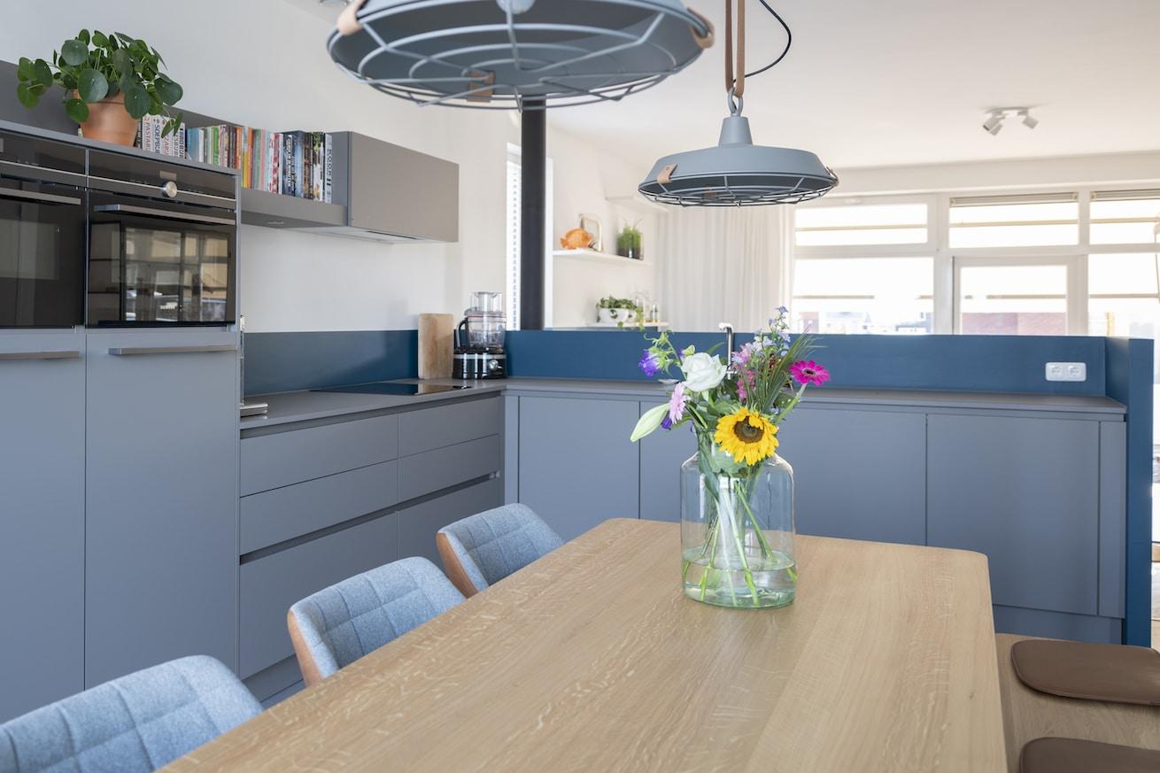 Mat grijze L-keuken met een trendy afwerking