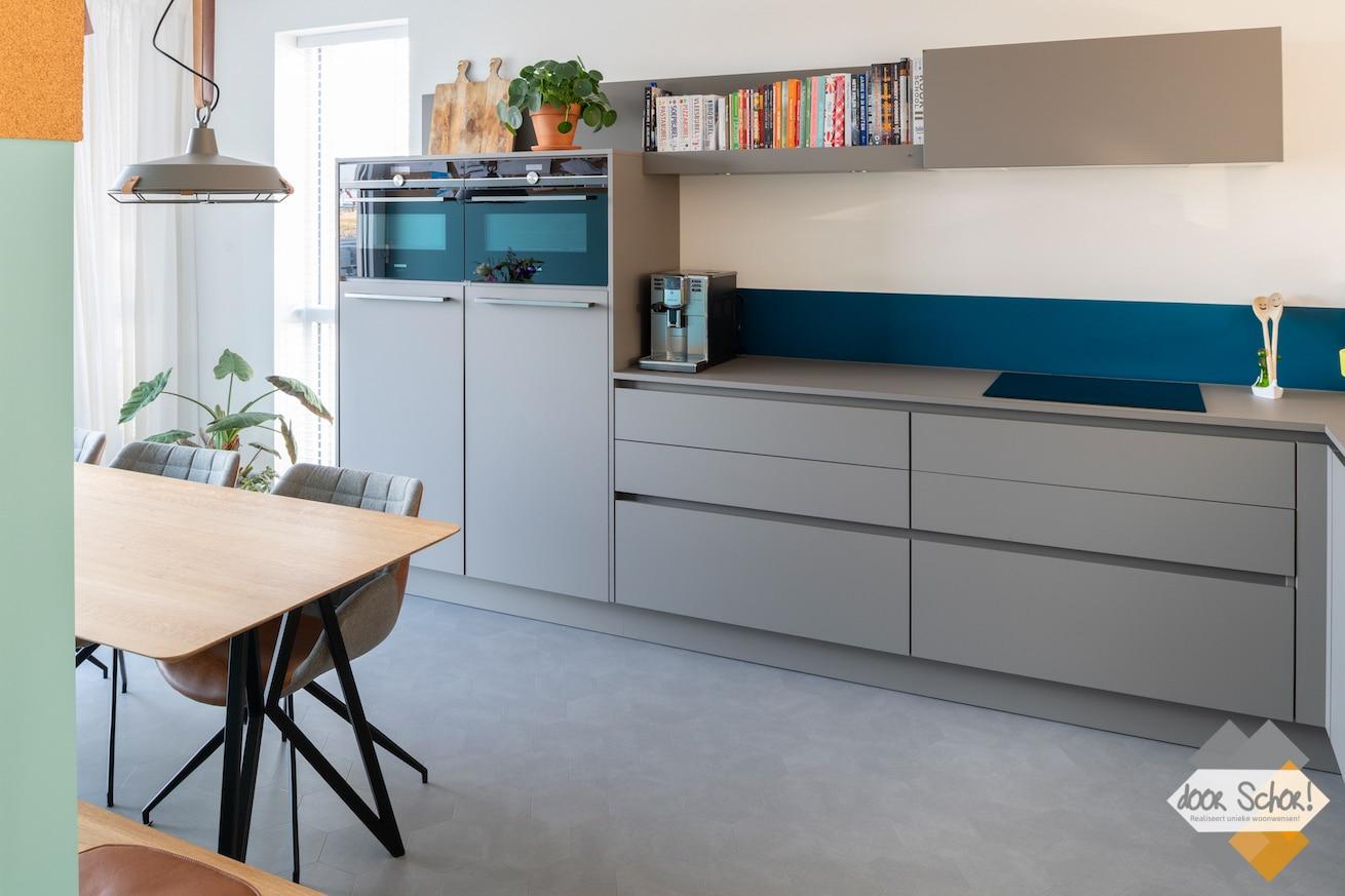 Mat grijze keuken met een greeploos design vanuit een andere hoek