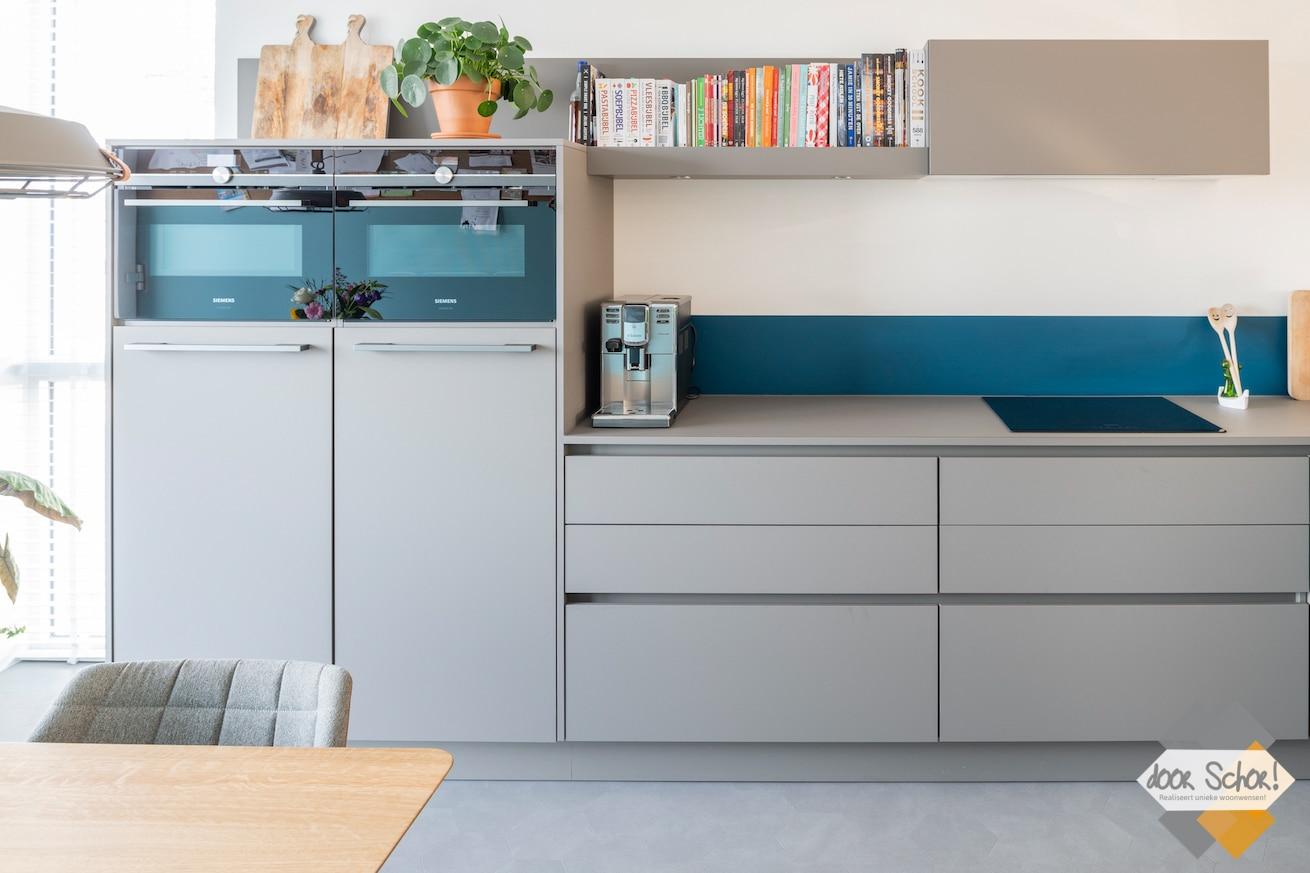 Een mat grijze keuken met een greeploos design