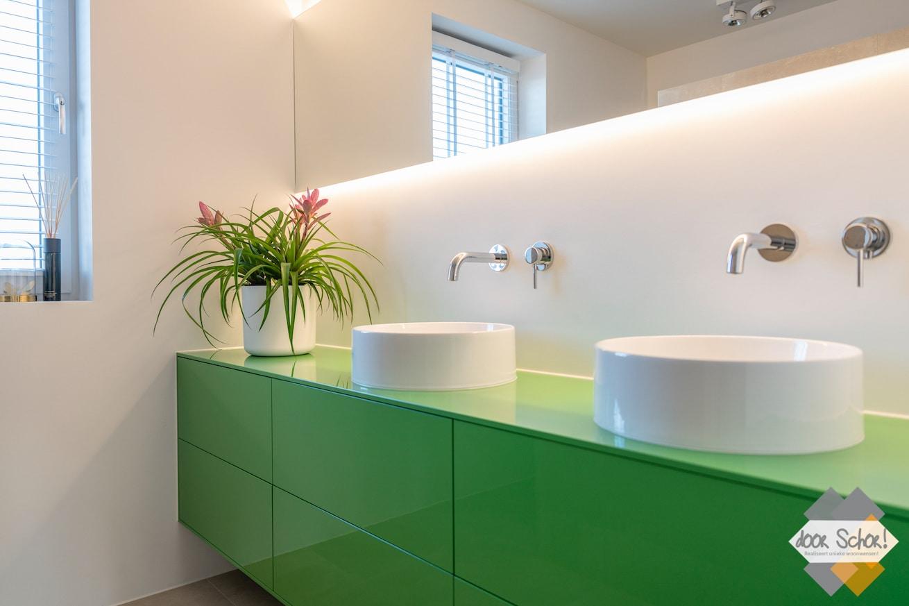 Een knal groen maatwerk badkamer meubel met twee witte kommen
