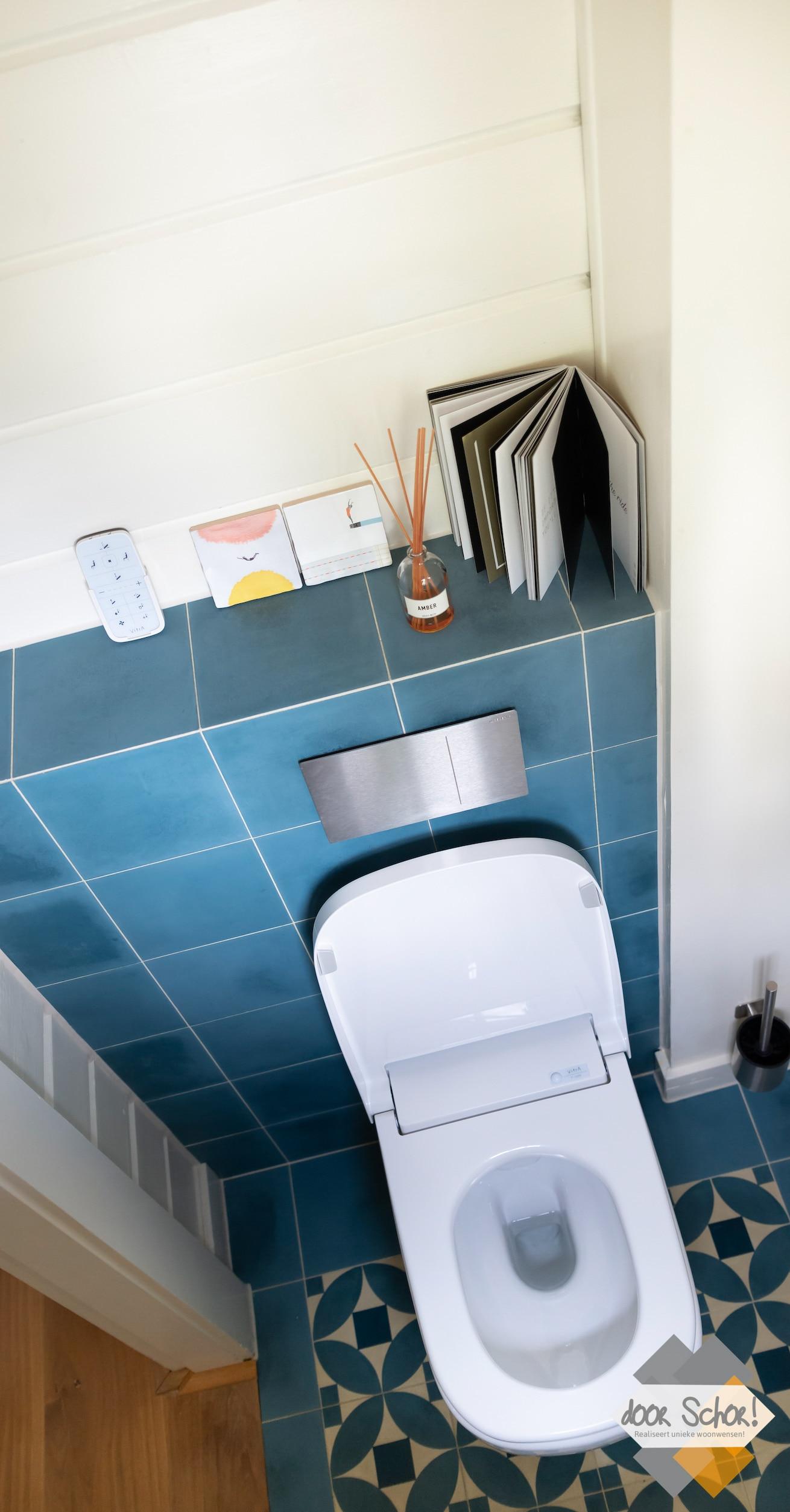 Electronisch toilet met blauwe tegels en houten achterwand