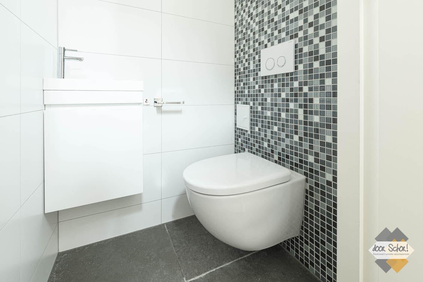 Toilet met kleine tegeltjes en strak witte afwerking